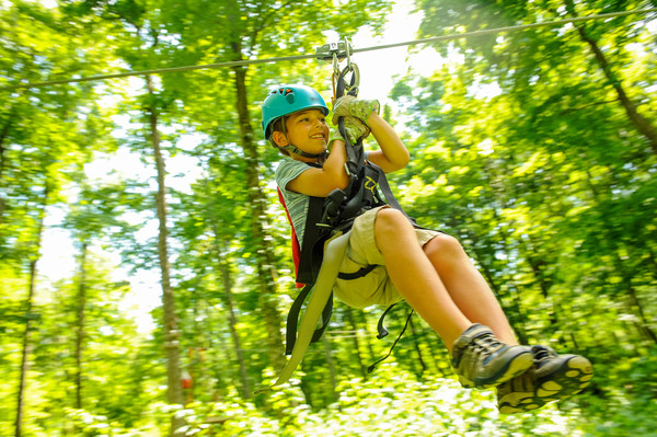 boy zipping on zipline through wooded area